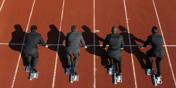 Businessmen lined up on a race track to represent getting back on track