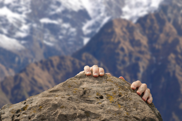 Climber reaching their goaland representing achieving business goals by using a high interest business account
